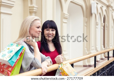 Two happy smiling women shopping with colored bags