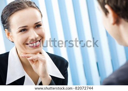 Two happy smiling young businesspeople, or business woman and client, working at office