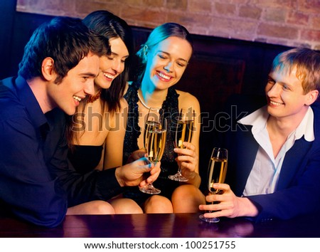 Two happy smiling young couples with champagne at celebration, party or romantic date at club