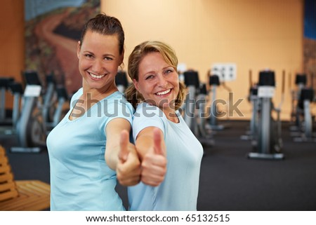 Two happy sporty women standing in a gym and holding their thumbs up