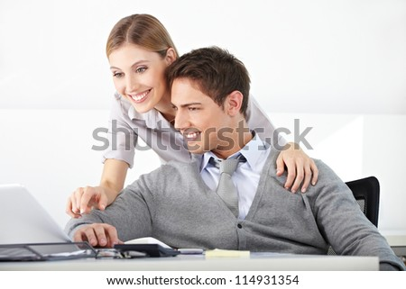 Two happy students working at laptop computer in the university