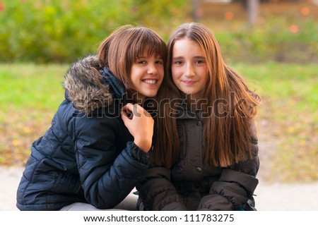 Two happy teenage girls having fun in the park on beautiful autumn day.