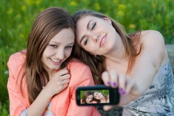 Two happy teenage girls taking selfshot or selfy picture of themselves with mobile phone portrait