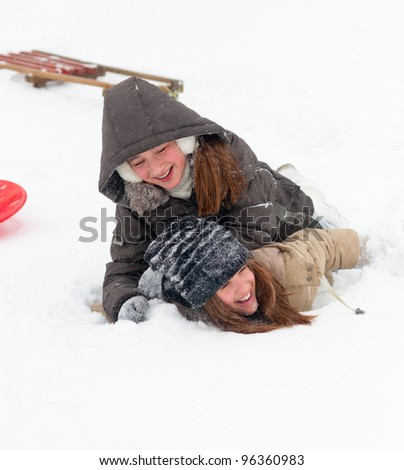 Two happy teenage girls wrestling in thick winter snow.