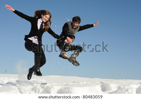 two happy teenagers jump through snowdrift