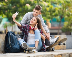 Two happy teenagers smiling and doing selfie together on the smartphone outdoors