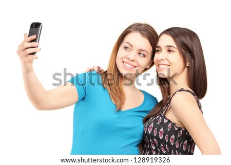 Two happy teenagers taking pictures of themselves with a cell phone isolated on white background