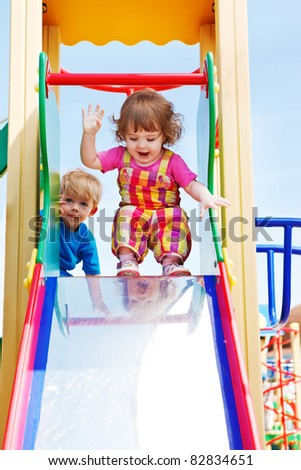 Two happy toddlers ready to slide down