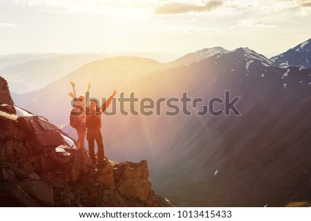 Two happy tourists backpackers are greetings sunset with raised hands. Travel success concept with place for text #1013415433