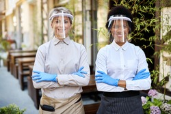 Two happy waitress wearing protective gloves and visors while standing with crossed arms at outdoor cafe.