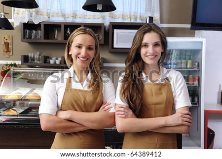 Two happy waitresses working at a cafe - stock photo