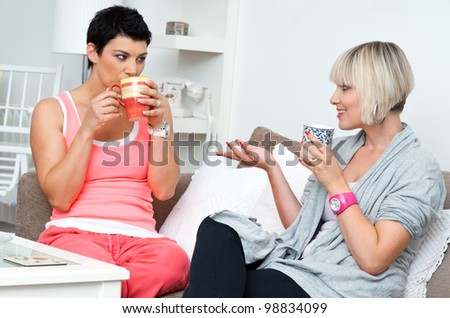 two happy woman friends chatting and smiling over coffee and cakes - stock photo