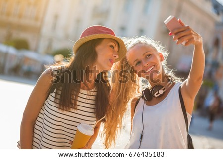 Two happy women are having nice time together in the city. They are taking selfie. #676435183