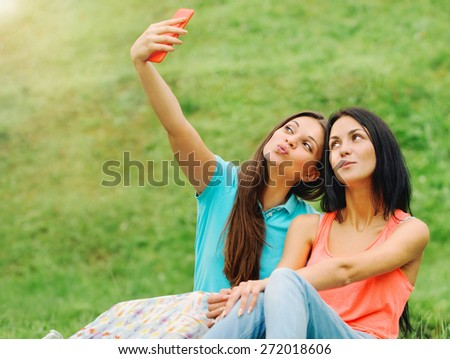 two happy women friends laughing and sharing social media pictures in a smart phone on picnic at the park, lifestyle concept