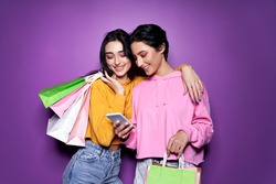 Two happy women friends shoppers holding shopping bags using mobile apps for online shopping standing on purple background. Retail ecommerce fashion sale offers, mall discounts in applications concept
