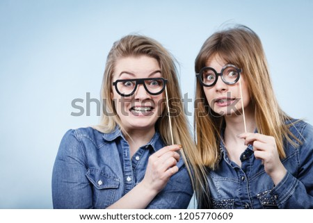 Two happy women holding fake eyeglasses on stick having fun fooling around wearing jeans shirts. Photo and carnival funny accessories concept. #1205770609
