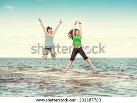 Two happy women jumping in the sea  - stock photo