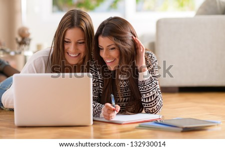 Two Happy Women Looking At Laptop While Lying On Floor