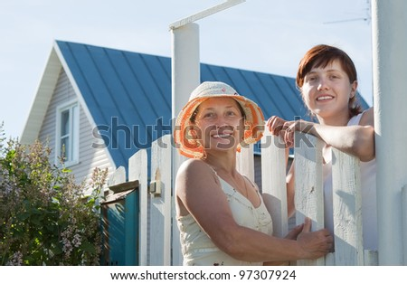 Two happy women near fence wicket  in front of home - stock photo