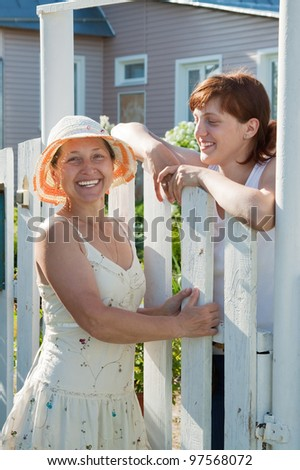 Two happy women near fence wicket  in front of home