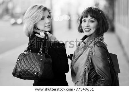 Two happy women on a street - stock photo