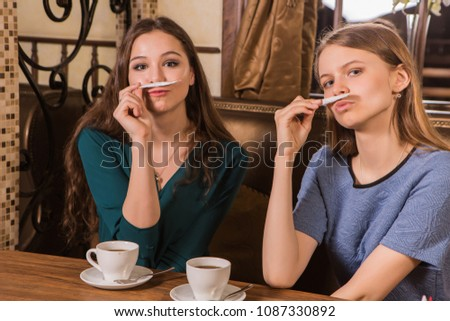 Two happy women plaing with sugar in a cosy cafe #1087330892