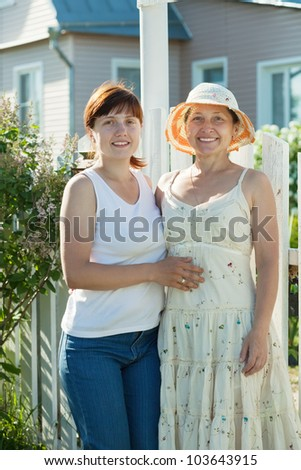 Two happy women posing in front of his  residence