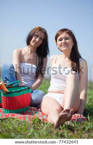 Two happy women relaxing outdoor in grass - stock photo