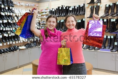 Two happy women with shopping bags against  counter in underwear shop