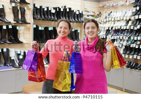 Two happy women with shopping bags at  shoes shop