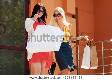 Two happy women with shopping bags on the steps