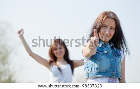 Two happy women with thumb up