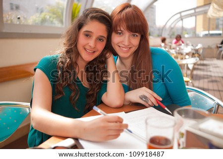 Two happy young beautiful women studying