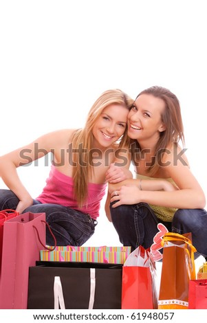 Two happy young beautiful women with the purchases - on white