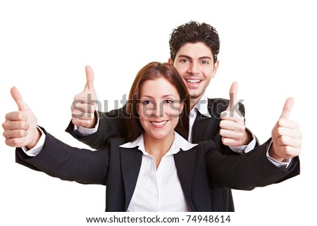 Two happy young business people holding their thumbs up