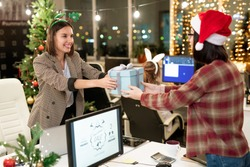 Two happy young businesswomen giving presents to each other over computer monitor on Christmas day in office