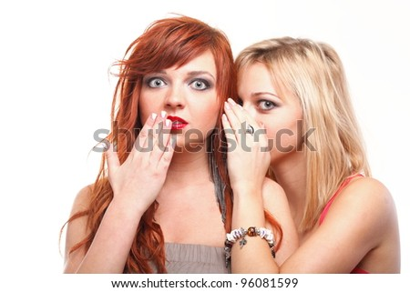 two happy young girlfriends blond and ginger talking white background - society gossip, rumor, rumour