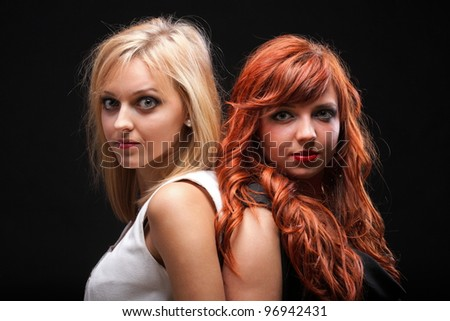 two happy young girlfriends blonde and red-hair black background Glamour