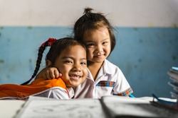 Two happy young girlfriends in the thai school. Thai school in a small village