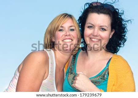 Two happy young girlfriends laughing and hugging