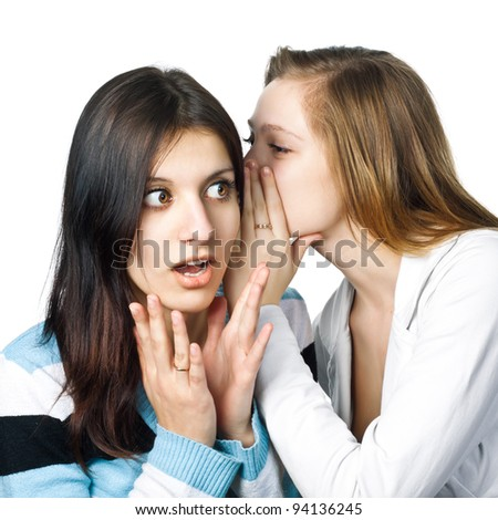 Two happy young girlfriends share secrets