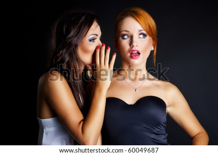 two happy young girlfriends talking over black