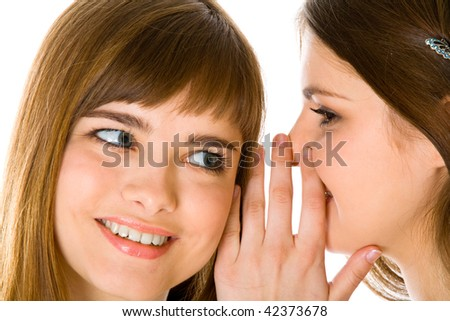 Two happy young girlfriends telling secret. Isolated on white background
