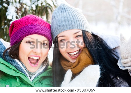 Two happy young girls having fun in winter park