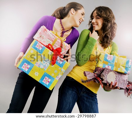 Two happy young girls holding presents