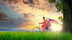 Two happy young local boy riding old bicycle at paddy field holding a Malaysian flag with beautiful sunset moments. Independence Day concept