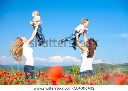 Two happy young mothers with children in the poppy field
