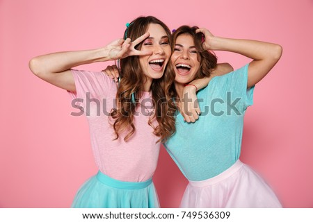 Two happy young woman in colorful clothes showing peace gesture, looking at camera, isolated over pink background