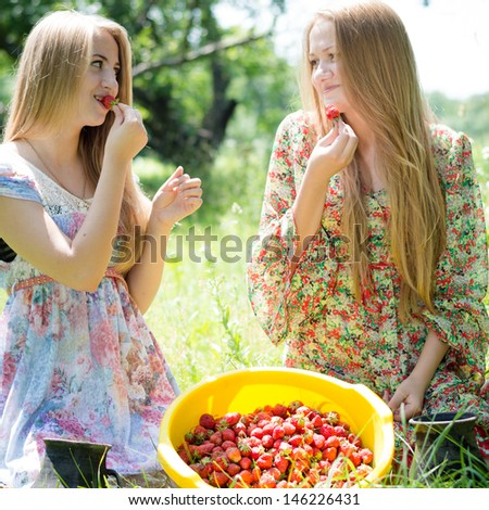 Two happy young women gathering strawberry on bright summer day