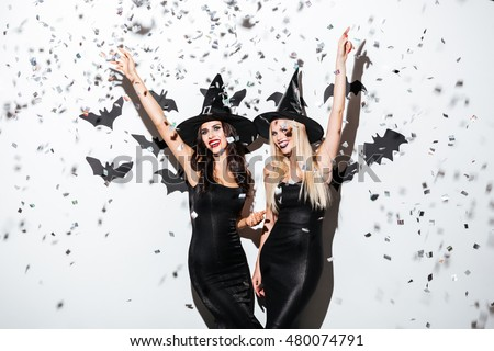 Two happy young women in black witch halloween costumes on party over white background #480074791